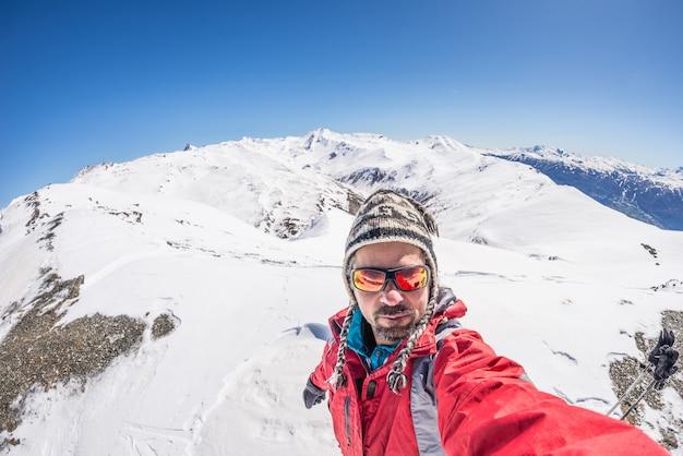Sciatore adulto alpino con barba, occhiali da sole e cappello, prendendo selfie sul pendio nevoso nelle splendide alpi italiane con cielo blu chiaro. concetto di voglia di viaggiare e avventure sulla montagna