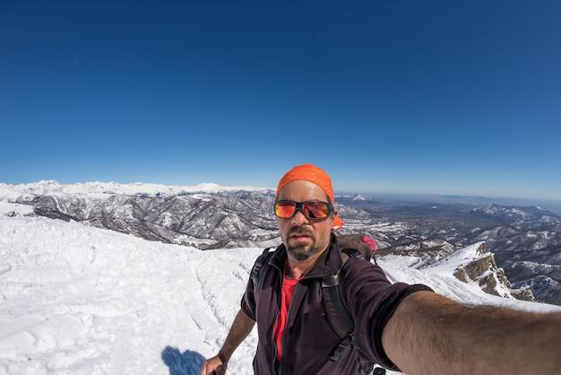 Sciatore adulto alpino con barba, occhiali da sole e cappello, prendendo selfie sul pendio nevoso nelle splendide alpi italiane con cielo blu chiaro. immagine tonica, stile vintage, obiettivo fisheye ad angolo ultrawide.