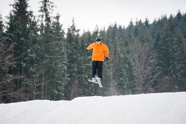 Sciatore al salto dal pendio delle montagne
