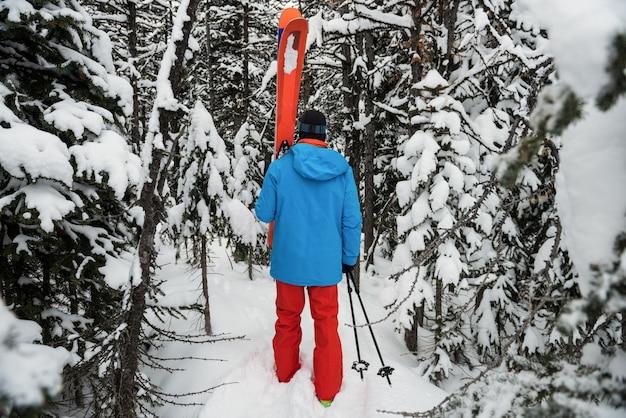 Sciatore che cammina con lo sci sulle montagne innevate