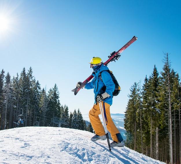 Sciatore che cammina su per il pendio