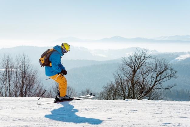 Sciatore che gode di sciare in montagna in una giornata invernale di sole