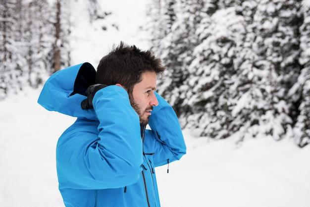 Sciatore che indossa giacca con cappuccio su montagne innevate