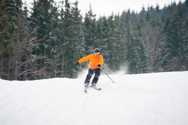Sciatore che scia in discesa dopo il salto in alto alla stazione sciistica contro ski-lift e pendio di neve