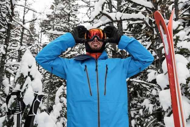 Sciatore che si aggiusta gli occhiali da sole
