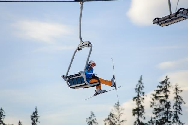 Sciatore che si siede all'elevatore di pattino contro cielo blu
