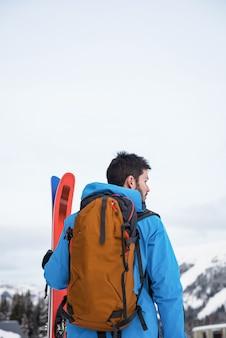 Sciatore che sta con lo sci sulle montagne innevate