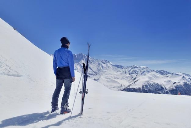 Sciatore che stanging davanti alla montagna nevosa