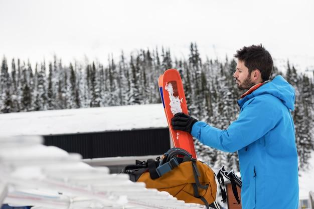 Sciatore che tiene i cieli sulle montagne nevose