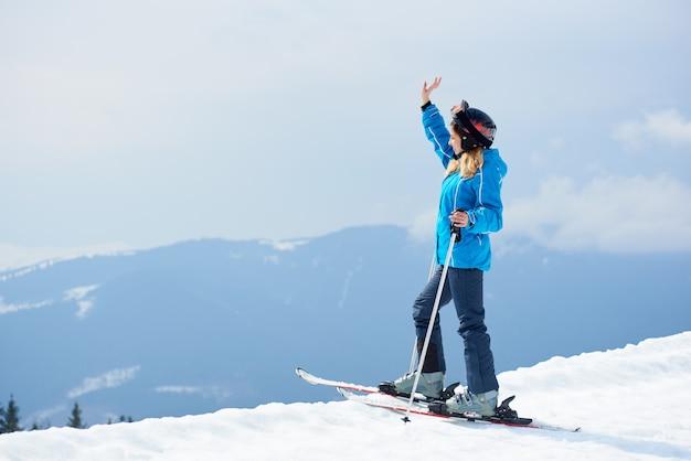 Sciatore della donna che gode di sciare alla stazione sciistica nelle montagne