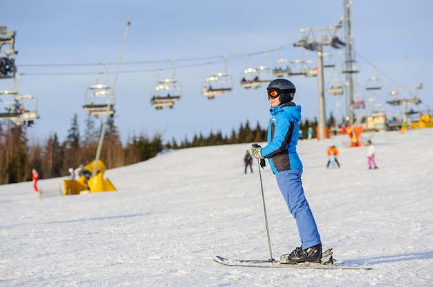 Sciatore della donna che scia in discesa alla stazione sciistica contro lo ski-lift