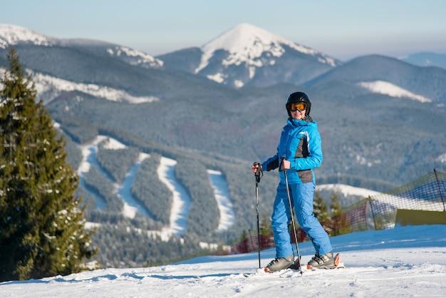 Sciatore della donna che sorride allegro alla macchina fotografica mentre sciando nelle montagne alla stazione sciistica di inverno
