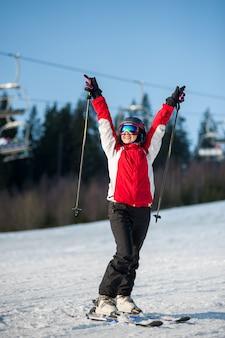 Sciatore della donna con lo sci al ricorso del winer nel giorno soleggiato
