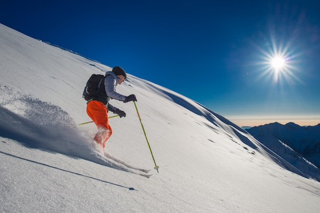 Sciatore di backcountry in neve fresca
