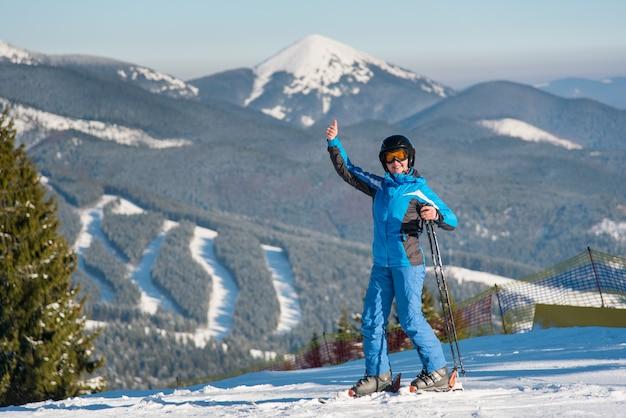 Sciatore donna felice sorridendo con gioia alla telecamera, mostrando i pollici mentre sciare in montagna