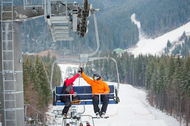 Sciatore e snowboarder in sella agli impianti di risalita