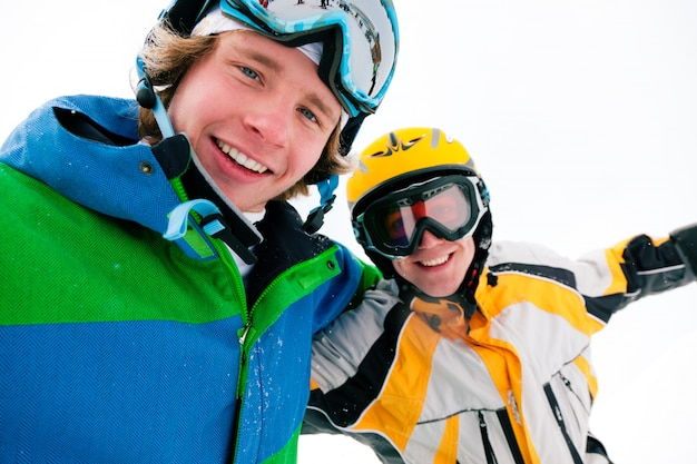 Sciatore e snowboarder nella neve