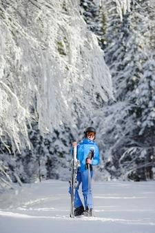 Sciatore felice della donna su una pista da sci nella foresta