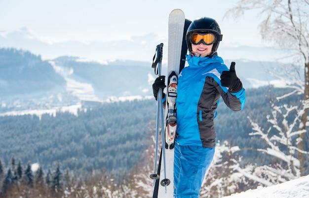 Sciatore femminile che mostra i pollici in su, in posa in montagna