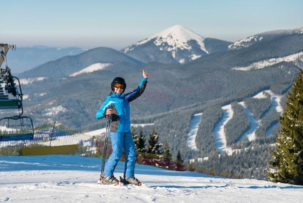 Sciatore femminile che mostra i pollici su mentre sciando