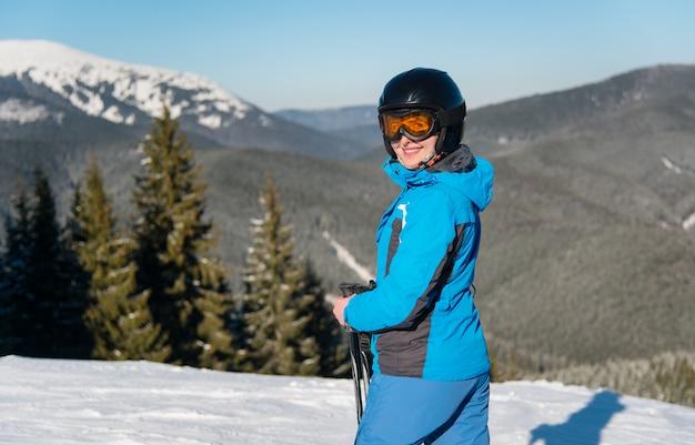 Sciatore femminile che sorride con gioia alla macchina fotografica mentre scia nella montagna un giorno di inverno soleggiato