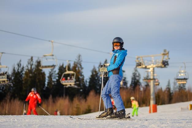 Sciatore femminile contro ski-lift e foresta in una giornata di sole