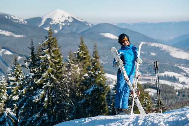 Sciatore femminile in cima alla montagna in giornata invernale di sole