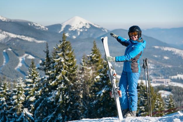 Sciatore femminile in piedi sulla cima di una montagna con gli sci in inverno resort, sorridendo, indicando il meraviglioso paesaggio naturale che la circonda