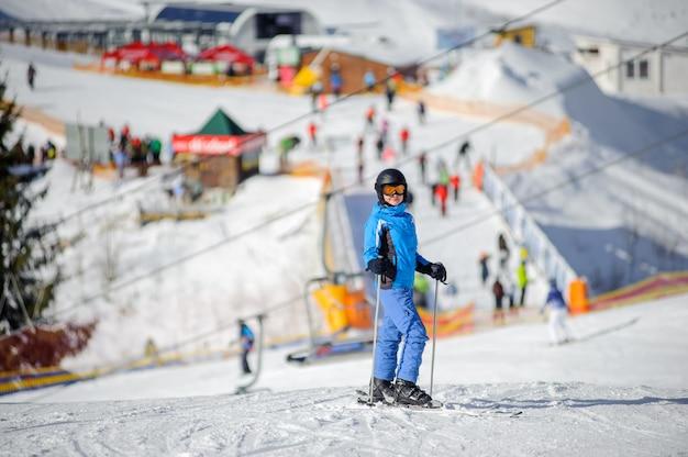 Sciatore femminile su una pista da sci in una giornata di sole