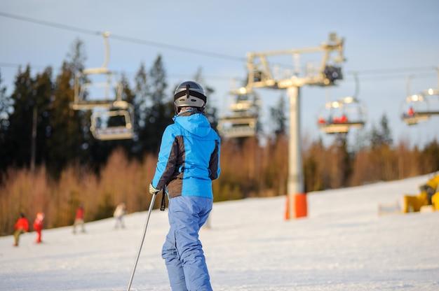 Sciatore in piedi su una pista da sci con ski-lift e foresta sullo sfondo la sera