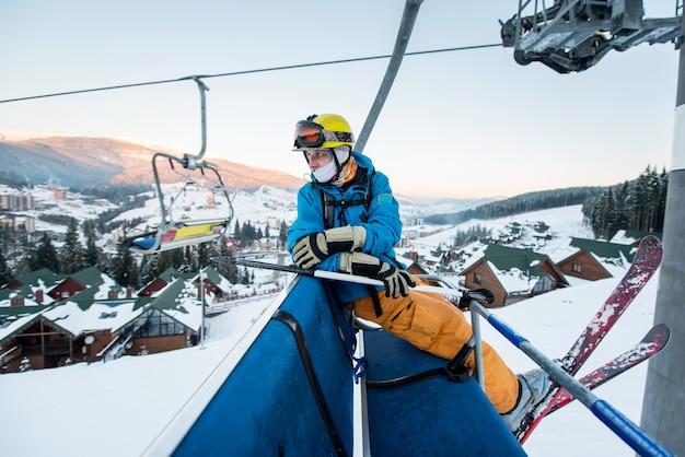Sciatore maschio professionista seduto alla seggiovia di sci la sera e torna indietro