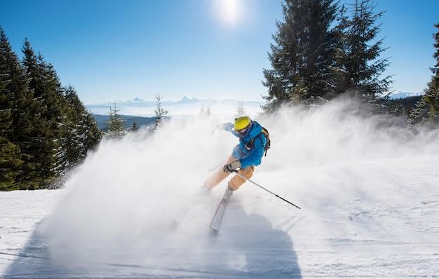 Sciatore maschio sciare sul pendio presso la stazione sciistica in montagna