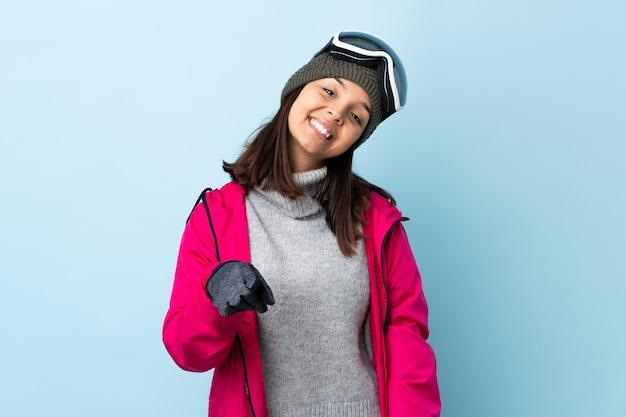 Sciatore ragazza con occhiali da snowboard che punta davanti con felice espressione