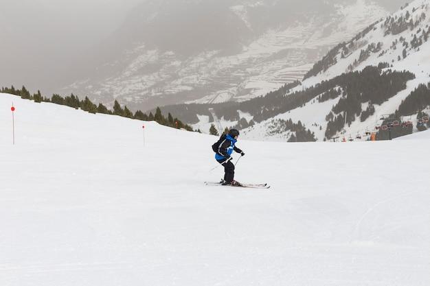Sciatore sciare sulla neve fresca e polverosa. stagione invernale. gli sport