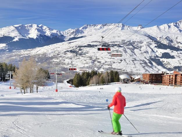 Sciatore sulle piste da sci nella località delle alpi francesi e seggiovia