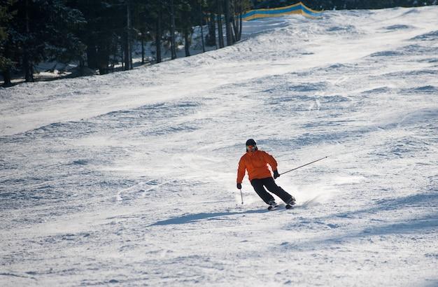 Sciatore uomo sci in discesa presso la stazione sciistica