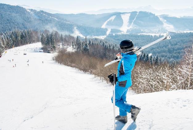Sciatrice che cammina lungo il pendio con gli sci sulla spalla