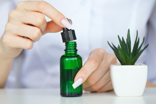 Scienza di cosmetici di bellezza, formulando e mescolando skincare con essenza di erbe, scienziato prepara materie prime organiche per prodotti di bellezza, medicina alternativa sana