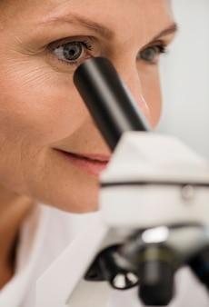 Scienziata che osserva tramite il microscopio