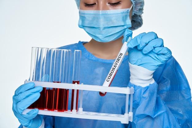 Scienziata in tuta protettiva chimica con la provetta al laboratorio per il risultato positivo del coronavirus. ricerca virus di covid-19