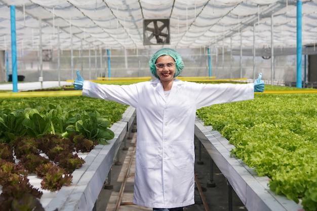 Scienziati asiatici della donna in serra idroponica organica.