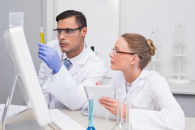Scienziati che esaminano il precipitato giallo in tubo