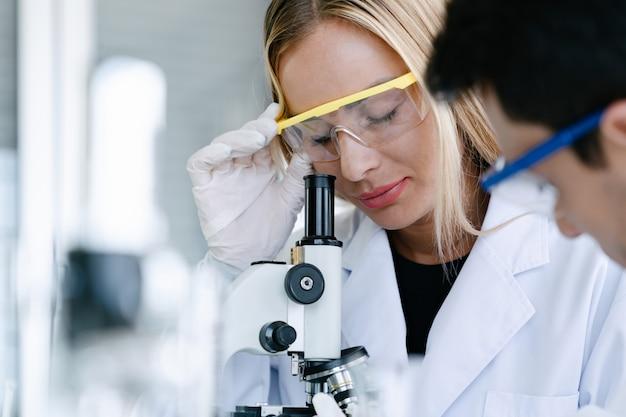 Scienziati che esaminano microscopio mentre fanno ricerca di sanità in laboratorio