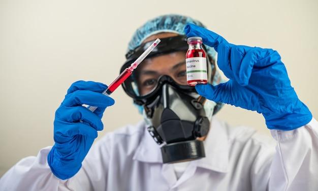 Scienziati che indossano maschere e guanti in possesso di una siringa con un vaccino per prevenire covid-19