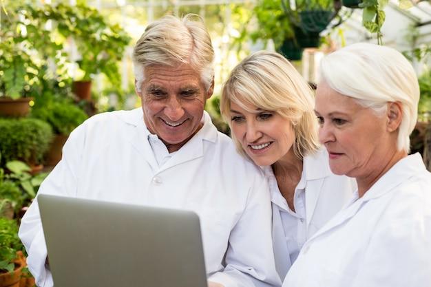 Scienziati che sorridono mentre discutono sopra il computer portatile