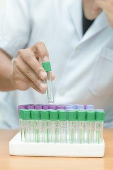 Scienziati dell'uomo tengono il tubo di vetro o la provetta