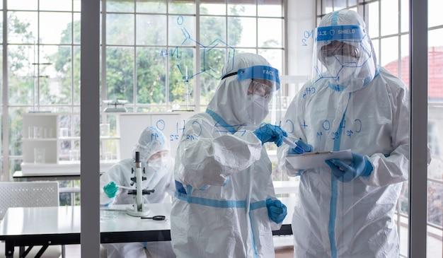 Scienziati e microbiologi con tuta dpi e maschera facciale in laboratorio calcolano la formula chimica per creare un vaccino o un medicinale per l'infezione da coronavirus.