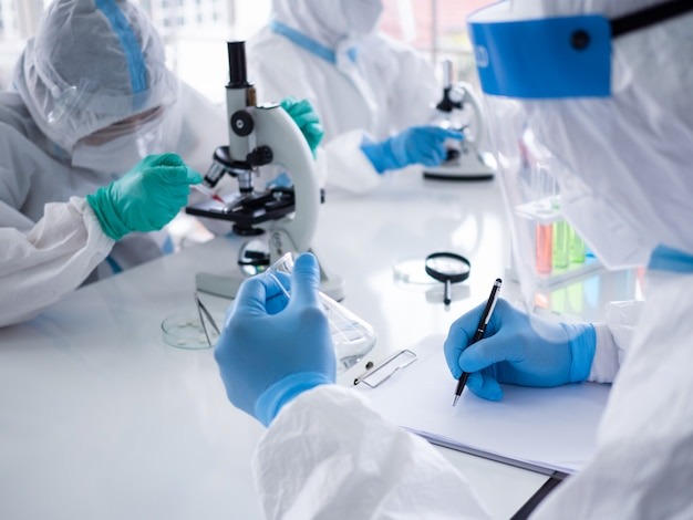 Scienziati e microbiologi con tuta in dpi e maschera facciale tengono in laboratorio una provetta e un microscopio, trovando un trattamento o un vaccino per l'infezione da coronavirus.