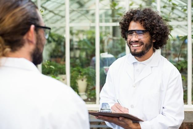 Scienziati maschi che sorridono mentre discutendo