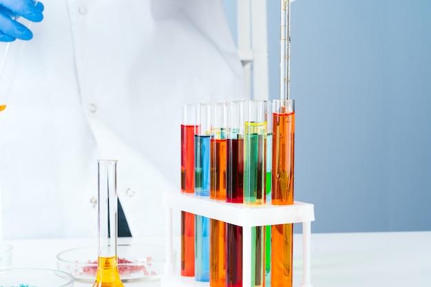 Scienziato che lavora con i campioni chimici nella fine del laboratorio in su
